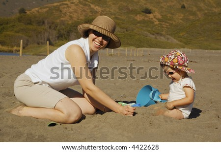 A young attractive mother looks up from playing with her toddler daughter in the sand on the beach (shot in San Francisco Bay Area). - stock photo