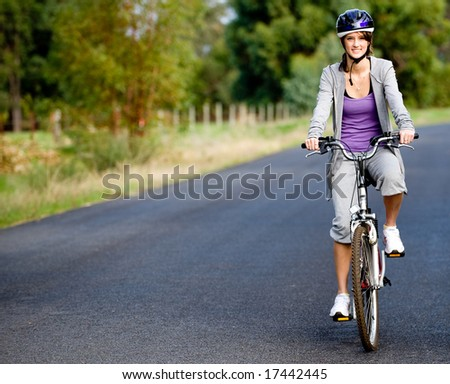 A young attractive woman cycling on a country road