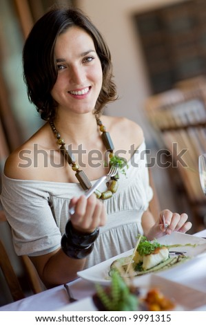 A young attractive woman eating a meal at a table outdoors - stock photo