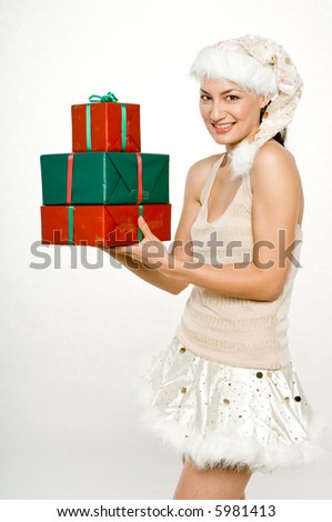 A young attractive woman in santa hat and skirt with gifts