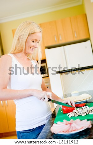 A young attractive woman in the kitchen making pizza