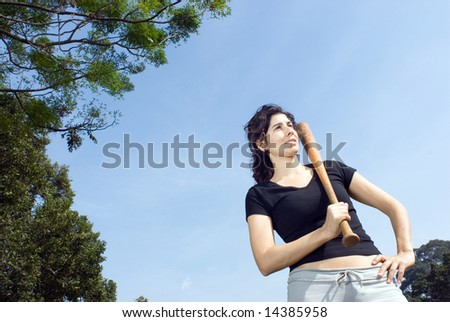 A young, attractive woman is standing in a park.  She is looking away from the camera, and posing with a baseball bat.  Horizontally framed photo. - stock photo