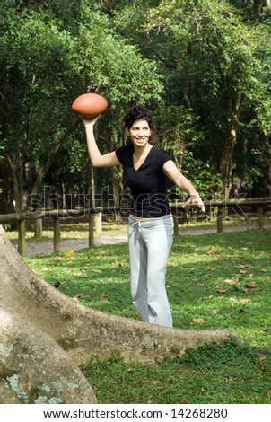 A young, attractive woman is standing next to a tree at the park.  She is smiling and about to throw a football.Vertically framed photo. - stock photo