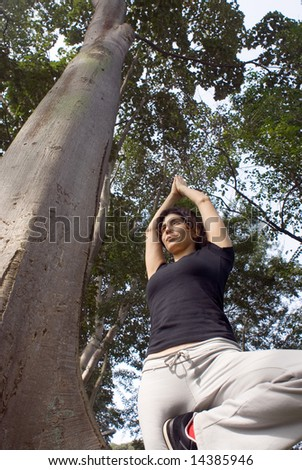 A young, attractive woman is standing next to a tree in a park.  She is performing yoga and stretching.  The camera is looking up at her, and she is looking away from it.  Vertically framed photo. - stock photo