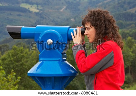 A young attractive woman looking through a telescope. Blurred background - stock photo