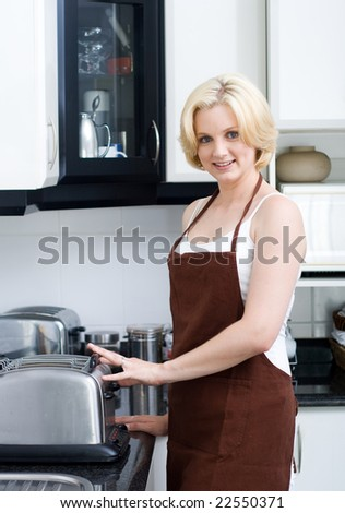 A young attractive woman making breakfast in the kitchen - stock photo