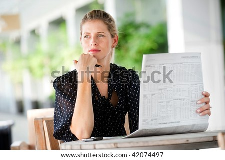 A young attractive woman reading newspapers at a cafeteria - stock photo