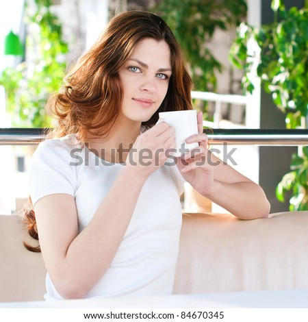 A young attractive woman sitting in a cafe with a coffe - stock photo