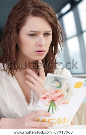 A young attractive woman sitting in a cafe with menu - stock photo