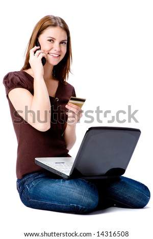 A young attractive woman with laptop, credit card and mobile phone on white background - stock photo