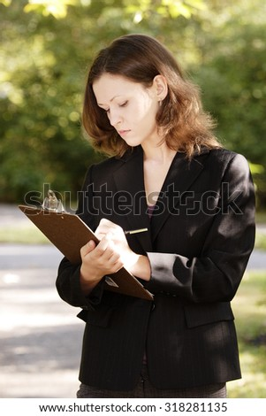 A young attractive woman writes on a clipboard. - stock photo