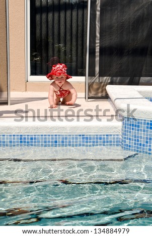 A young baby crawls through the opening of the safety fence left open. No adults appear to be near the child as she moves toward the swimming pool. - stock photo