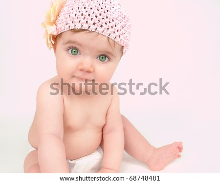 A young baby girl is wearing a flower hat and looking into the camera. She is sitting on the floor. - stock photo