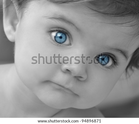 A young baby is in black and white with bright blue eyes. Use it for a child or parenthood concept.