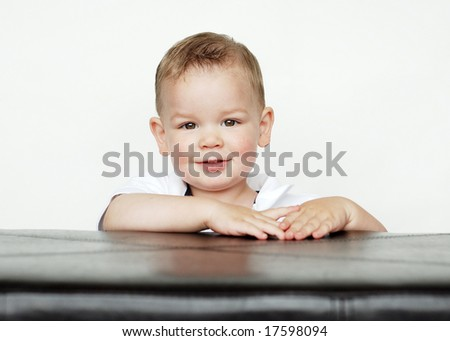 A young baby is posing for the camera in a studio.  Horizontally framed shot. - stock photo