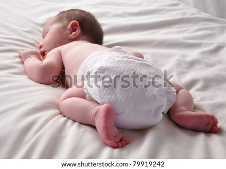 A young baby is sleeping on a bed with white sheets. The newborn is wearing a white diaper. - stock photo