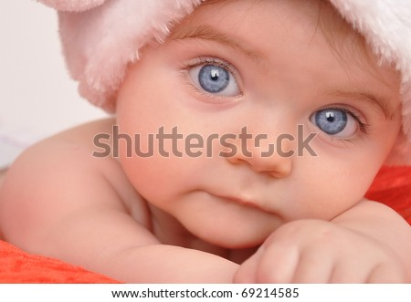 A young baby is staring at the camera wearing a Santa Christmas hat. - stock photo