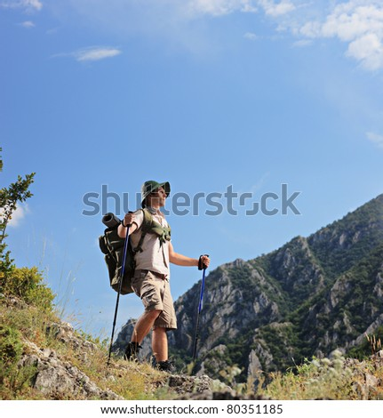 A young backpacker looking towards the summit in Macedonia - stock photo