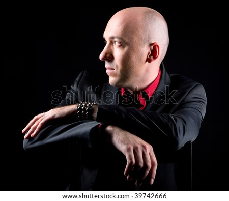 A young bald man in a black suit - stock photo