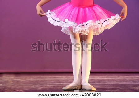 a young ballerina in first position rehearsing on stage - stock photo