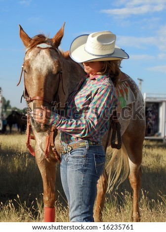 A young barrel racer spends a quiet moment with her horse before the competition. - stock photo