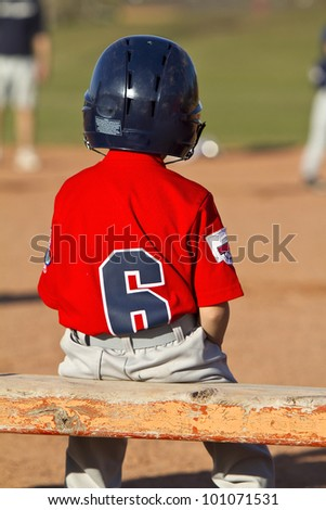 A young baseball player sitting on the bench - stock photo
