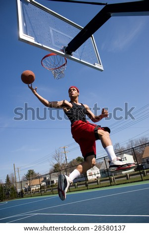 A young basketball player driving to the hoop. - stock photo