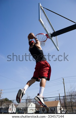 A young basketball player driving to the hoop for a slam dunk. - stock photo