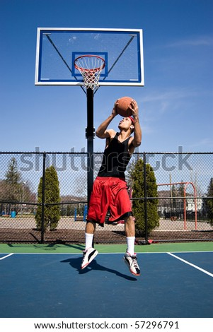 A young basketball player driving to the hoop with some fancy moves.