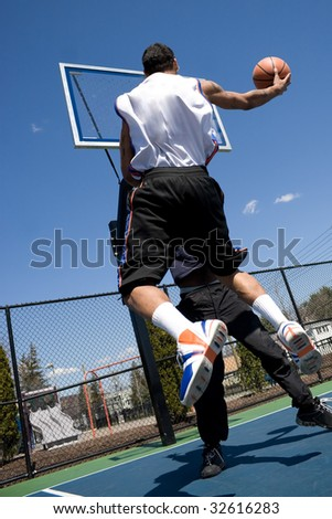 A young basketball player driving to the hoop with some fancy moves during a one on one game at the park. - stock photo