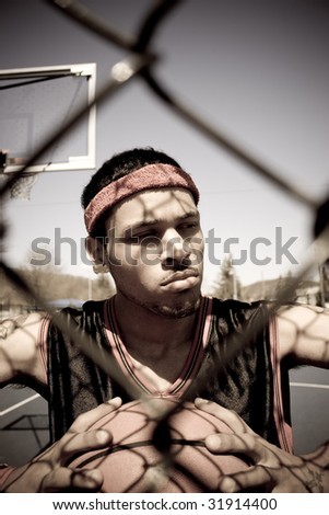 A young basketball player gripping the ball tightly as viewed through the chain linked fence. - stock photo