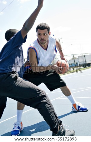 A young basketball player guarding his fierce opponent during a game of one on one at the park. - stock photo