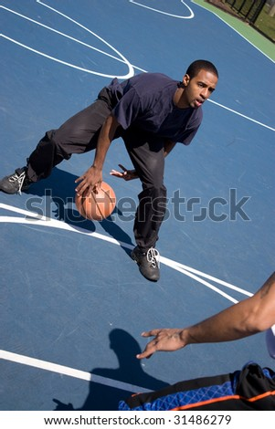 A young basketball player posts up against his opponent during a one on one basketball game. - stock photo