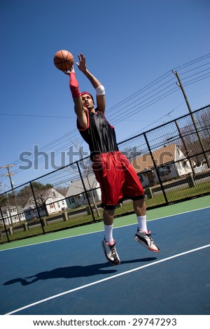A young basketball player shooting a three point jump shot. - stock photo