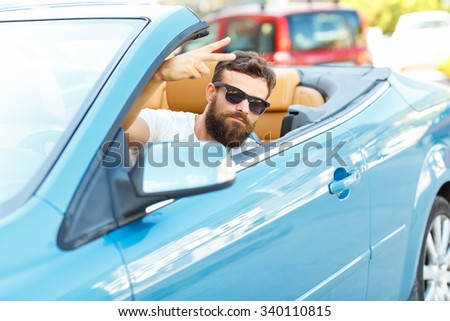 A young bearded man sitting in a convertible -  - the concept of buying a used car or a rental car - stock photo