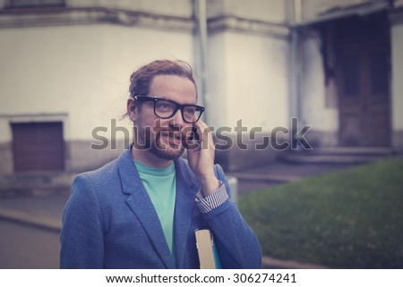 A young bearded man, who is a student or a teacher is on the phone. At hand is holding a book. - stock photo