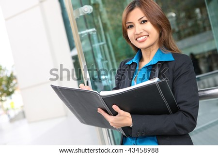 A young, beautiful asian business woman at office building