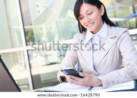 A young, beautiful asian business woman with pda organizer - stock photo