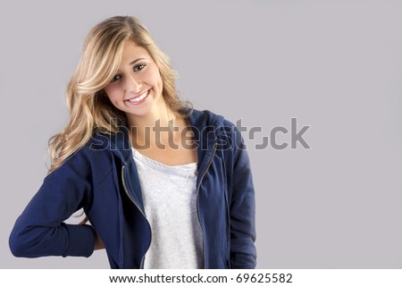 a young beautiful blond teenage girl posing in a blue athletic suit.