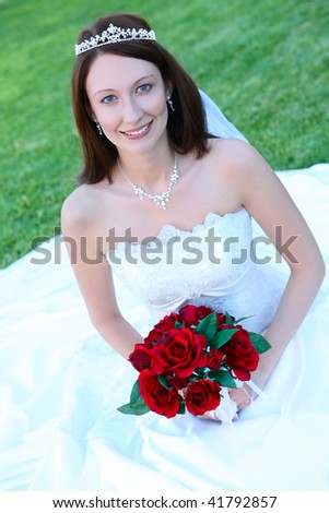 A young beautiful bride woman at her wedding on the grass - stock photo