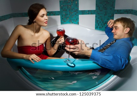 A young beautiful couple enjoying a bath with wine in a glass and looking at each other - stock photo