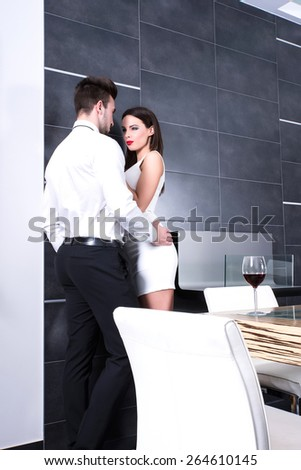 A young beautiful couple flirting in the living room. - stock photo