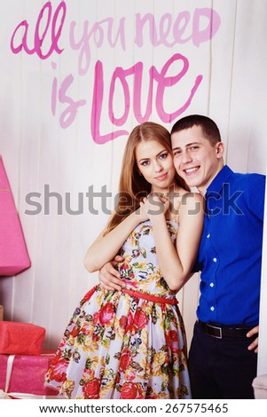 A young beautiful couple is embracing near a studio wall with caption love. - stock photo