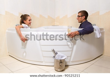 A young beautiful couple is enjoying a bath with champagne in a glass and looking at each other - stock photo
