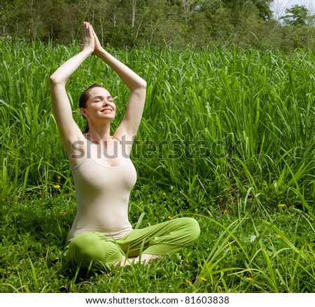 A young beautiful fit woman meditating outdoors in green grass - stock photo