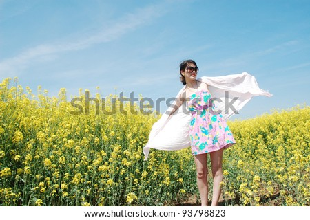 A young beautiful girl enjoying a sunny day in a field of canola flowers. - stock photo