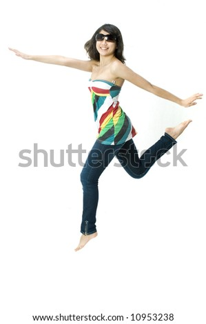 A young beautiful girl in a bright top with sunglasses jumping - stock photo