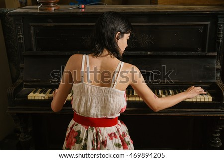 A young beautiful girl in a dress is playing the piano