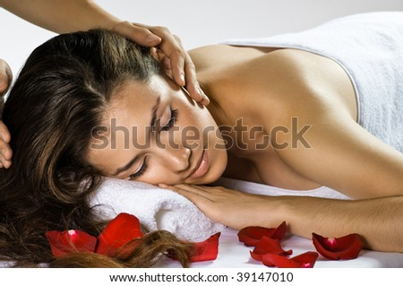 a young beautiful girl is being massaged - stock photo