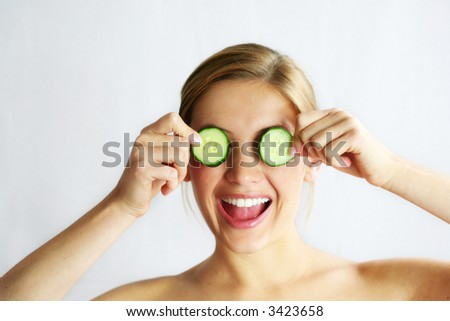 a young, beautiful, happy woman is holding some cucumber in front of her smiling face - stock photo